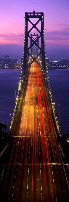 The Old Bay Bridge in San Francisco, with heavy traffic trails at sunset.