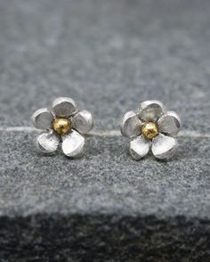 Pretty pair of daisy stud earrings with a brass or copper bead in the centre.  Each daisy measures 8.5mm which has been saw pierced from silver sheet and shaped to form the flower.  The earrings have been finished with matte petals and are secured with silver pegs and butterflies.  #brass #copper #daisy #earrings #flower #handmade #silver #starboardjewellery #jewellery #cornwall #uk #gb #westcountry #devon #england #silversmith #pretty #jeweller #jewellers #handmadejewellery