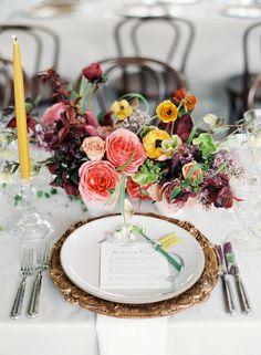 Colorful centerpiece + elegant chargers: http://www.stylemepretty.com/2016/05/31/yellow-rustic-durham-ranch-wedding/   Photography: Jose Villa - http://josevilla.com/