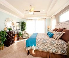 Gorgeous light blue walls line this beautiful bedroom. A blue and brown bedspread is centered in front of a dark brown dresser and mirror.