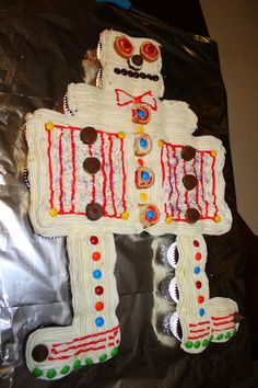 Xander's 7th Bday - Robot cupcake cake. Head (4), shoulders (4), body (24), legs/feet (8) = 40 cupcakes & 4 (!!) cans of Pillsbury whipped supreme vanilla frosting (piped in lines straight across all the cupcakes). Swirly eyes and buttons are Little Debbie strawberry shortcake roll ups, buttons and details are M&Ms, mini Reeses cups & Hershey kisses.