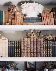 Antique objects and books on shelves in French inspired library/Kay O'Toole