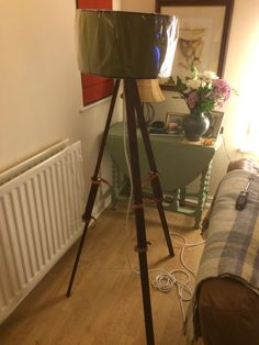 Mahogany style and leather strap tripod lamp.