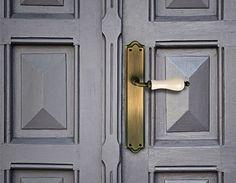Se trata de un juego de manillas en bronce combinado con porcelana beige sobre una puerta lacada en gris.Destaca su estilo elegante y clásico.