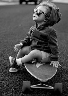 black white toddler Skater Girl in sunglasses sitting on skateboard waiting to grow big enough to ride go skateboarding I want a pic of the kids like this
