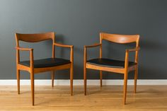 This is a pair of vintage Mid-Century teak dining chairs with arms designed  by Henry Rosengren Hansen for Vamo Sonderborg. The seats have been  professionally reupholstered in black faux leather. We have a set of eight  matching dining chairs available separately to make a set of ten.  $1400/pair MIDCENTURY MODERN FINDS