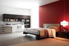 A modern, young bedroom with a large double bed and composition of furniture in light colors and dark wood-effect finishes. In this composition: bedroom with double bed, bedside tables, wall-mounted bookcase, shelves, drawer units, cabinets, wall-mounted desktop and large wardrobe.