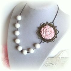 Vintage style handmade necklace starts of w/ a beautiful blooming vintage pink rose flower that I carved using polymer clay. Followed by white shell pearls in 12mm, a lovely chain in antique gold finish, and a clasp for closure at the back. Flower sits atop a beautiful vintage flower filigree in antique gold finish as well.