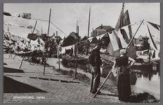 SPAKENBURG, Haven 1950-1956. Wasgoed aan de roop dwars over de straat aan de haven met botters. Op de voorgrond een vrouw zonder kraplap in kulder met boormouwtjes, gehaakte muts, effen werkschort zonder stukje, met gesloten gatbanden. #Utrecht #Spakenburg