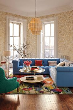 The sitting room of Eva Chen, Lucky's editor in chiefliving room with blue corner sofa gold wallpaper and modern floral rug