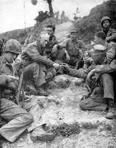 Ernie Pyle shares a cigarette with Marines on Okinawa 1945.