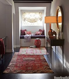 """In the second-floor hallway of a California house, designer Betsy Burnham overlaps Turkish runners from Rugs & Art, drawing the eye to a Moroccan-inspired reading nook. The vintage carpets """"can transform a plain hallway into a decorated space,"""" Burnham says."""