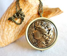 Music box locket, round locket with music box inside, in bronze with art nouveau maiden on front cover