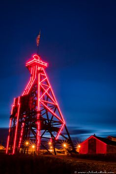 """The Original"" mining headframe in uptown Butte, Montana is lit up at night by colored lights."