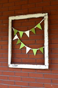 """Simple, shabby summer porch decor: pennants cut from 4""""x1/4"""" balsa wood, sawn at 20 degrees & stapled to twill tape. (Or use jute, ribbon, whatever you like. I always default to twill tape because of its herringbone weave.) Balsa is so soft that I used a desktop stapler to avoid splintering. Secure to cup hooks on the back of a salvaged window frame, et voila! UPDATE: I've recently seen unfinished pennant shapes at Michael's. A little pricier, but certainly quicker!"""