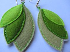 I was inspired by the new growth in Central Park and geometric shapes when I made these felt earrings. The oval shape earrings in green hues are reminiscent of leaves or organic insect wings. These are very light weight and wearable and are created by hand using only 100 percent wool felt.    From the top of the earring hook to the bottom point of the blossom is about 3 1/2 long.