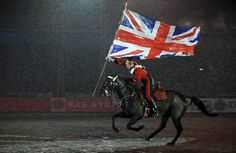 A soldier on horseback from The Household Cavalry Mounted Regiment races across the arena at the Windsor Castle Royal Tattoo in pouring rain while holding the Union Flag aloft. Photographer Sgt Ian Houlding; Crown copyright.