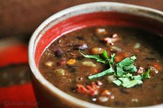 Hearty black bean soup with ham hocks, sweet potatoes, bell pepper, onion, cumin, chili, and molasses.  Garnish with cilantro, sour cream, and avocado. ~ SimplyRecipes.com