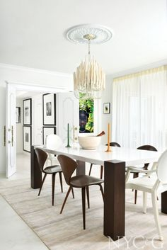 The dining room includes a Z Gallerie table, a quartet of Norman Cherner–designed walnut chairs, and a pair of armchairs designed by Philippe Starck for Kartell. The Tilda chandelier is from Arteriors. #NYC&G