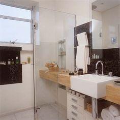 A bancada de mármore travertino gialo vai de parede a parede neste banheiro de 5 m² – inclusive o boxe foi recortado sobre ela.