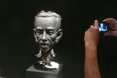 """A visitor takes a photo of """"Jokowi"""", a caricatured statue created by Beby Charles, at the Sculpture and Installation Art Exhibition entitled """"Attitude, Consistency, Challenge"""" at the Cipta 2 Gallery, Taman Ismail Marzuki (TIM) arts center in Jakarta. Joko Widodo, better known by his nickname Jokowi, is Jakata's mayor and a prospective Republic of Indonesia presidential candidate. The exhibition runs through Nov. 15, 2013. (Antara/Dodo Karundeng)"""