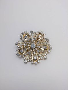 Check out this item in my Etsy shop https://www.etsy.com/listing/574364096/vintage-rhinestone-flower-brooch-vintage