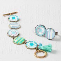 Boho Armband mit Glascabochons, Fassungen, Motivbögen und Troddeln.