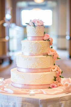 Four tiers of gorgeous! Love the pink ribbon and roses cascading down this classic wedding cake! {Studio L Photography}