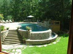 The infinity edge of this pool spills over a natural stone wall, creating a beautiful and relaxing waterfall effect. By Signature Outdoor Concepts.