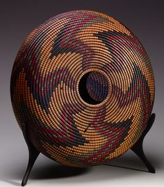 "David Nittmann has mastered the art of optical illusions.  What appear to be intricately woven baskets are actually turned wood bowls, platters and bodydrums (a hollow vessel that can be used as a musical instrument or as an art object). He  turns, burns and dyes the wood used in his internationally renowned Basket Illusion series.  Here: 14"" dia Bodydrum"