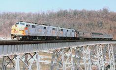 Louisville & Nashville EMD E-7 diesel electric locomotive # 780, leading another, is seen hauling a short passenger train across a steel trestle along the mainline at Covington, Kentucky, 1971