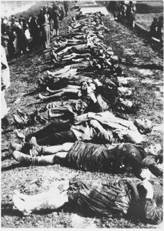Sisak concentration camp. A group of men and women view the bodies of concentration camp victims that have been laid out in a row on the banks of the Sava River.