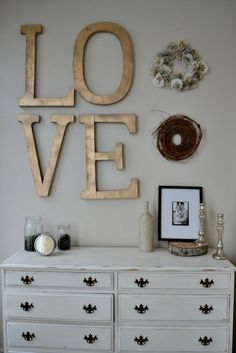 "Golden words ""LOVE"" on wall with a couple canvases would be gorgeous."