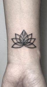 Lotus flower on wrist by Fin Tattoos