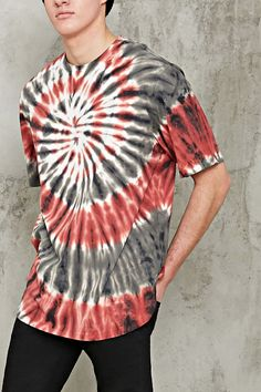 A knit tee in a tie dye wash featuring dropped shoulder creating a slightly oversized silhouette, short sleeves, a crew neck, and a vented high-low hem.