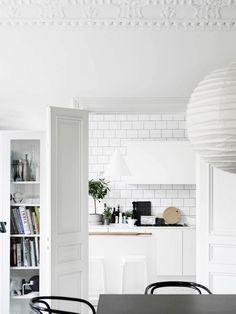 Bright white kitchen space with french doors, a large white lantern, and white subway tile backsplash