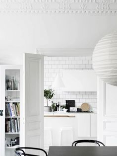 Bright white kitchen space with french doors, a large white lantern, and white subway tile backsplash