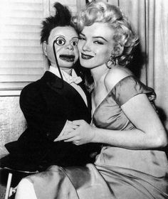 Marilyn Monroe holding a Charlie McCarthy Doll.