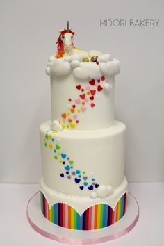Rainbow Unicorn 3-tiered celebration cake with hand cut hearts, hand molded clouds and unicorn by Midori Bakery