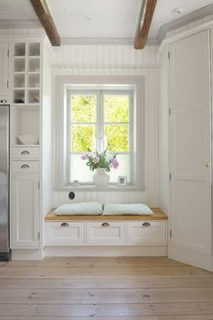 space by refrigerator for bottles . window seat/storage . natural look . drawers under windowseat . floor .