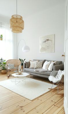 Bright and modern living room with a grey couch, a white rug and a light wooden floor. We love the Eames rocking chair, the woven pendant light and the curved floor lamp. #WhiteRugs #LampWohnzimmer