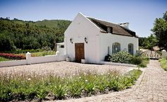 Traditional Cape Dutch thatched stone cottage in white with wood double doors Beautiful Interiors, Beautiful Homes, South African Homes, African House, Cape Dutch, Dutch House, Best Boutique Hotels, Luxury Accommodation, Cottage Interiors