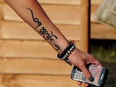 woman forearm script tattoo placement