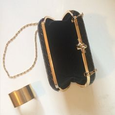 "Black Clutch w/ Gold Chain A gorgeous woven faux leather hard shell clutch with a gold knot clasp closure. So classy & chic. Roomy enough to fit all your evening essentials. Includes a removable gold chain. Bottega Veneta inspired. Measures 7"" x 4"" x 2.25"". Chain 47"" long. New with Tags *Price Firm* Bags"