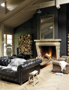 Double sided Black Chesterfield Sofa, bleached Woods, Matte Gray Walls, Stacked Wood & Fireplace. This is a Mans Room. #COUNTRY www.Chesterfields1780.com #chesterfields1780 #furniture #interiors #Chesterfields