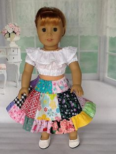 Mayellen is wearing a really colorful skirt with a white ruffled blouse. For the skirt, I used twenty five different cotton fabrics. It has elastic casing at the waistline. The blouse is made from a white voille fabric with raised dots. It has a neckline ruffle with tiny daisy crochet