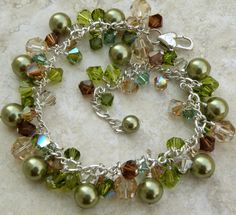 Luxe and unique autumn inspired Swarovski pearl bracelet is handmade with olive green Swarovski pearls, peridot green, smokey topaz, yellow topaz and tourmaline green Swarovski crystals. Hand wire wrapped with sterling silver wire, set on sterling silver chain and finished with a sterling silver heart lobster clasp. Gorgeous, attractive and makes for an impressive gift for a woman who loves sparkly unique artisan jewelry. A great mother of the bride or groom gift for your autumn wedding…