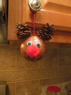 """Reindeer ornament made from styrofoam ball painted brown, googly eyes, red pom pom, and pine cones! Also used glitter glue to accent the """"antlers"""" for a little sparkle!"""