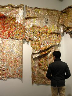 """Ghana artist El Anatsui, metal hanging at Brooklyn Museum. I love the way the artist recycles liquor bottle caps and other found objects to create gorgeous metallic """"fabrics"""" resembling the traditional Kente cloth woven in Ghana. Photo by Maeve Gately, 2013."""