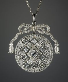 Pendant and chain, diamonds and platinum, the pendant in the form of an openwork roundel hung with ten square-cut diamond drops surmounted by a ribbon bow. Contained in the original Cartier red leather case with original brooch fitting and screwdriver, stored beneath the upper pad, the silk lining printed in gold. 1910